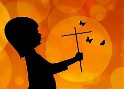 Kleines Kind mit Kreuz und Schmetterlingen